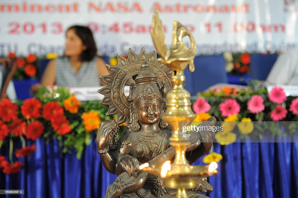 An idol of Goddess Saraswati (Goddess of Knowledge) is seen in the foreground as US astronaut of Indian-Slovenian origin Sunita Williams (L) visits Gujarat Technological University on the outskirts of Ahmedabad on April 6, 2013. Williams holds a world record for total cumulative spacewalk time by a female astronaut and has spent a total of 322 days in space on two missions. AFP PHOTO / Sam PANTHAKY
