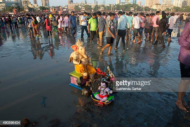 An idol of lord Ganesha is washed onto the shore after being immersed into the sea in Mumbai Ganesha Chaturthi or Ganapati festival is celebrated in...