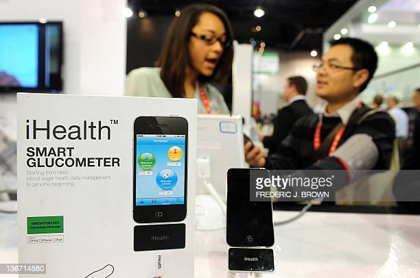 An iHealth rep offers a man a blood pressure checkup from a blood pressure monitoring system for iPod touch iPhone and iPad during a demonstration of...