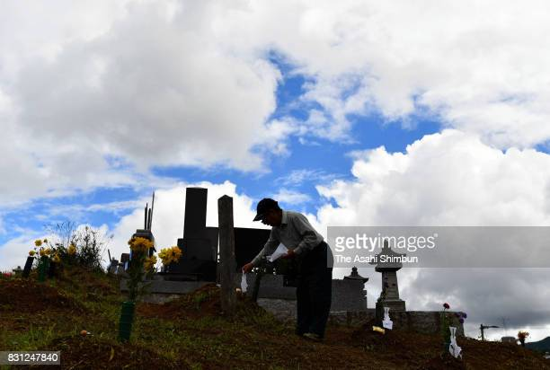 An Iitate Village resident offers a prayer at his ancesters' grave on August 13 2017 in Iitate Fukushima Japan The Obon or Bon season to honour...