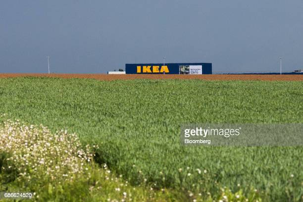 An Ikea AB store sits beyond agricultural fields where the Europacity shopping and leisure complex developed by Auchan Holding SA and Dalian Wanda...