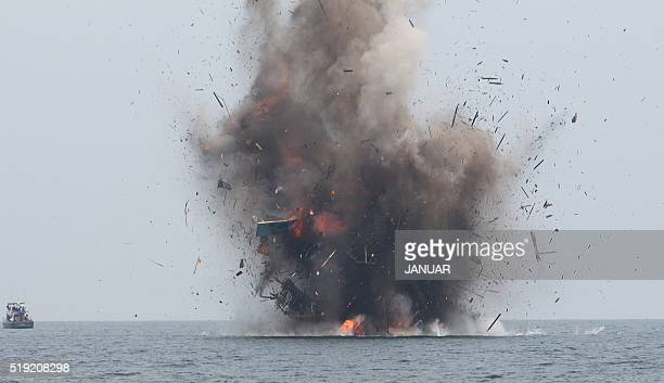 An illegal fishing boat is blown up with explosives by Indonesian authorities in Kuala Langsa Aceh province on April 5 2016 Indonesia sank 28 illegal...