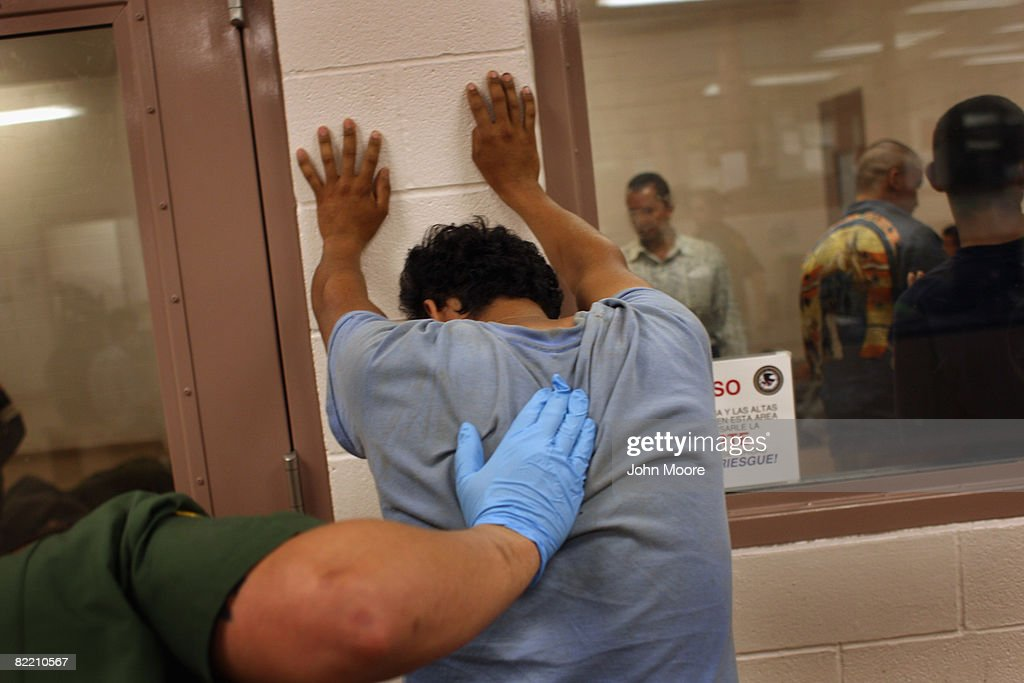 An illegal immigrant is body searched in a holding center at a US Border Patrol station after he was caught crossing from Mexico into the United...