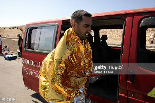An Illegal immigrant is seen covering himself with a thermal blanket as he waits to be sent to a temporary holding center for foreign nationals on...