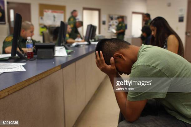 An illegal immigrant sits in a holding center at a US Border Patrol station after he was caught crossing from Mexico into the United States August 7...