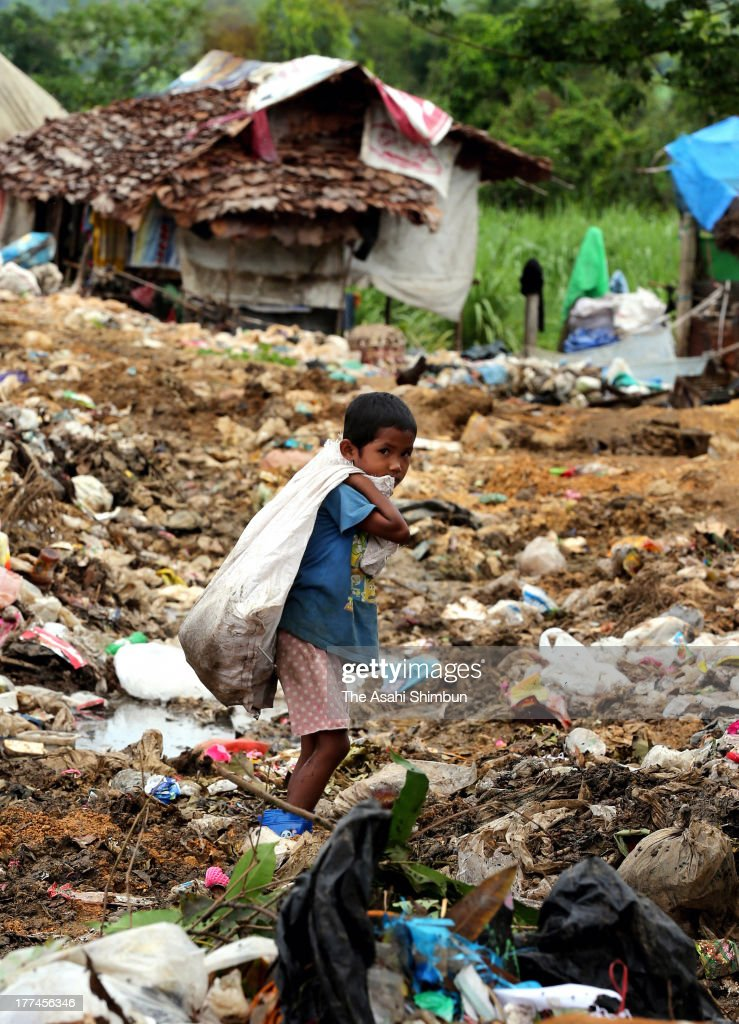 An illegal immigrants boy from Myanmar works at mountains of rubbish on July 18, 2013 in Mae Sot, Thailand. 500 people of 150 households live around the area, make a living by sorting out the rubbish. The life is 'still better' than Myanmar, according to an illegal immigrant.