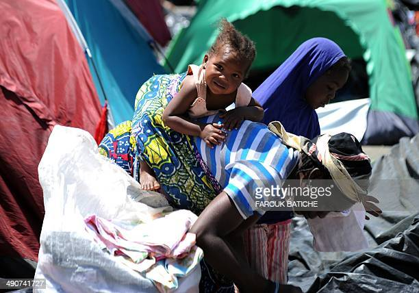 An Illegal migrant from Niger carries her child on May 14 2014 after settling with other migrants some of them for more than one year near the fruit...