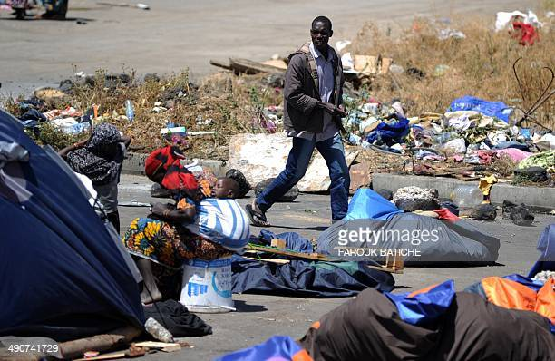 An Illegal migrant from Niger walks past tents on May 14 2014 after settling with other migrants some of them for more than one year near the fruit...