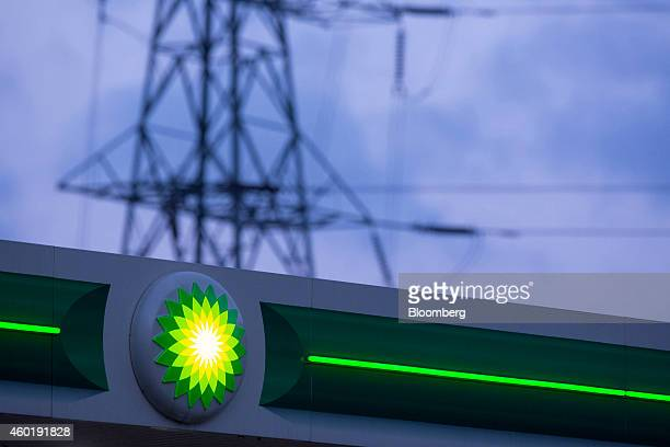 An illuminated BP logo sits outside a gas station operated by BP Plc as power transmission lines hang from an electricity pylon beyond the forecourt...