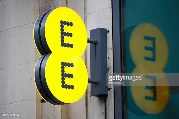 An illuminated EE logo is reflected in the window of an EE mobile phone store operated by Orange SA and Deutsche Telekom AG in London UK on Thursday...