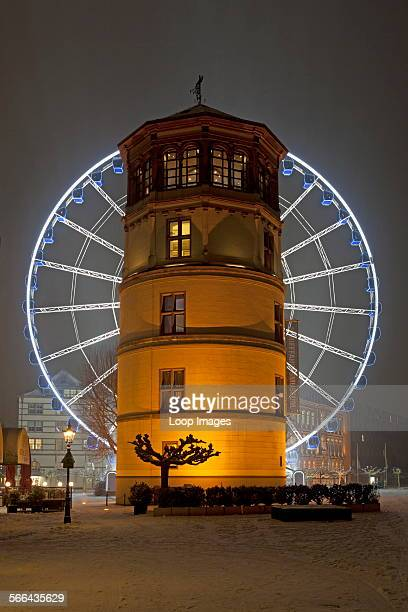 An illuminated ferris wheel behind the Shipping Museum tower in Dusseldorf