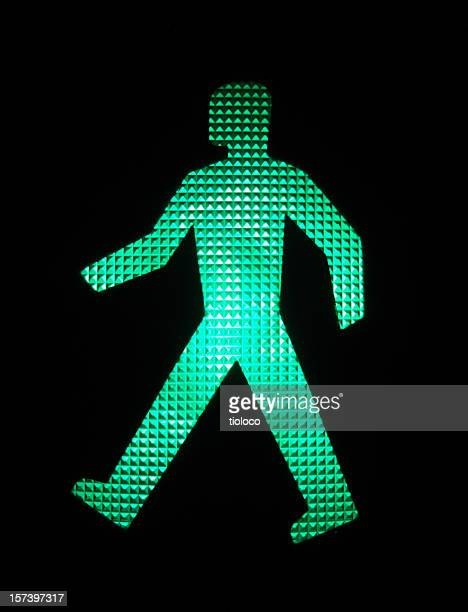 An illuminated green LED image of a walking person
