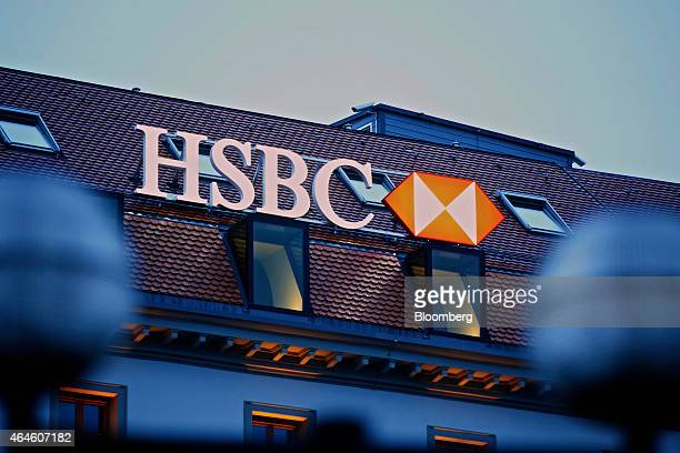 An illuminated HSBC logo sits on the rooftop of the building that houses HSBC Holdings Plc's private banking unit at dawn in Geneva Switzerland on...