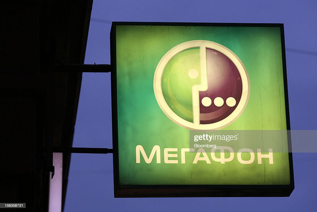 An illuminated logo is seen outside an OAO MegaFon mobile phone store in Moscow, Russia, on Thursday, Dec. 13, 2012. OAO MegaFon and its main shareholder billionaire Alisher Usmanov bought 50 percent of Euroset Holding NV in a deal that gives Russia's biggest handset retailer an enterprise value of $2.3 billion. Photographer: Andrey Rudakov/Bloomberg via Getty Images