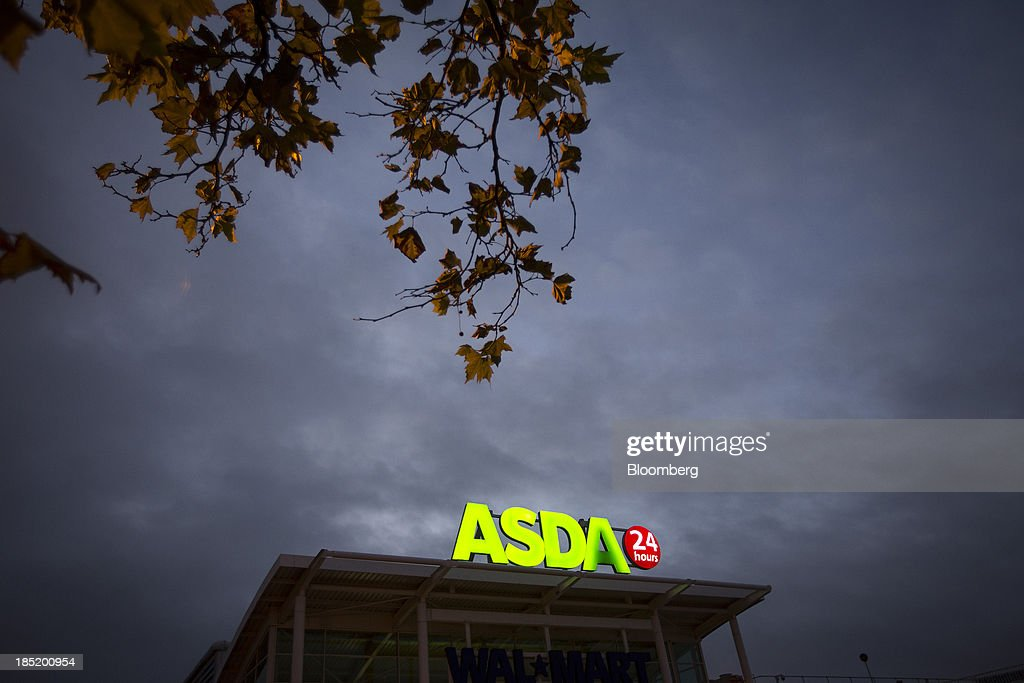 An illuminated logo sits above the entrance to an Asda supermarket, the U.K. retail arm of Wal-Mart Stores Inc., in Watford, U.K., on Thursday, Oct. 17, 2013. U.K. retail sales rose more than economists forecast in September as an increase in furniture demand led a rebound from a slump the previous month. Photographer: Simon Dawson/Bloomberg via Getty Images