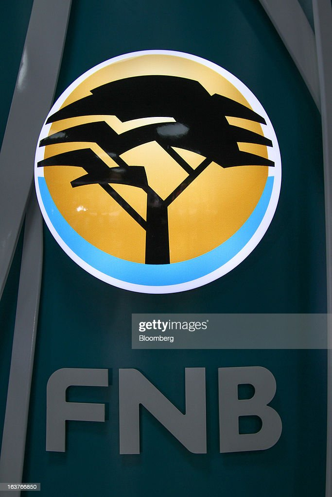 An illuminated logo sits on display at a First National Bank (FNB) branch in Johannesburg, South Africa, on Friday, March 15, 2013. A recovery in mining and manufacturing is giving South Africa's rand and bonds a breather amid concern that growth is slowing while inflation accelerates. Photographer: Nadine Hutton/Bloomberg via Getty Images
