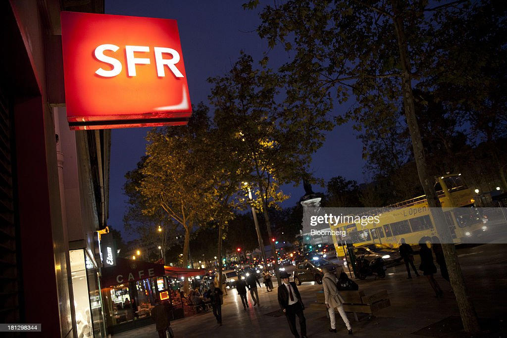 An illuminated logo sits on display outside an SFR store, a mobile-phone unit of Vivendi SA, near a street cafe in Paris, France, on Thursday, Sept. 19, 2013. Bank of France General Council member Bernard Maris said France will end up restructuring its debt as tax 'optimization' by large companies including Google Inc. will leave too big a burden on the middle class. Photographer: Balint Porneczi/Bloomberg via Getty Images