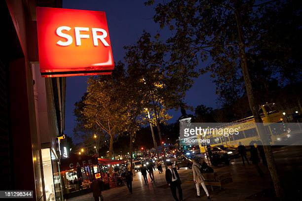 An illuminated logo sits on display outside an SFR store a mobilephone unit of Vivendi SA near a street cafe in Paris France on Thursday Sept 19 2013...