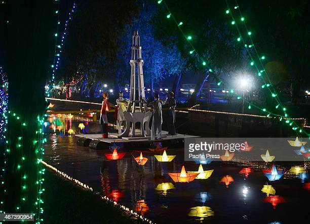 An illuminated view of the floats and lining trees decorated with festive lights in the canal in connection to the spring festival Lahoreis the...