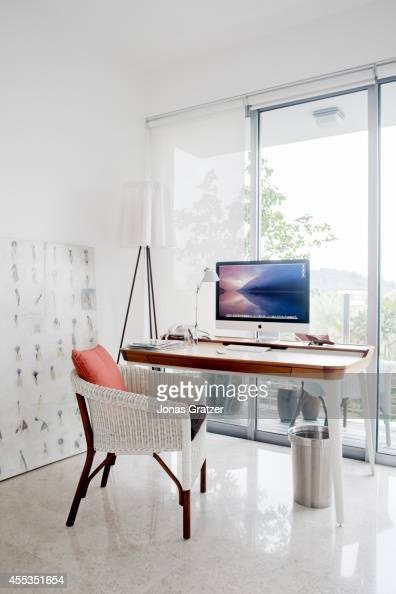 An iMac computer placed on a desk that overlooks the window of a Raffles hotel room