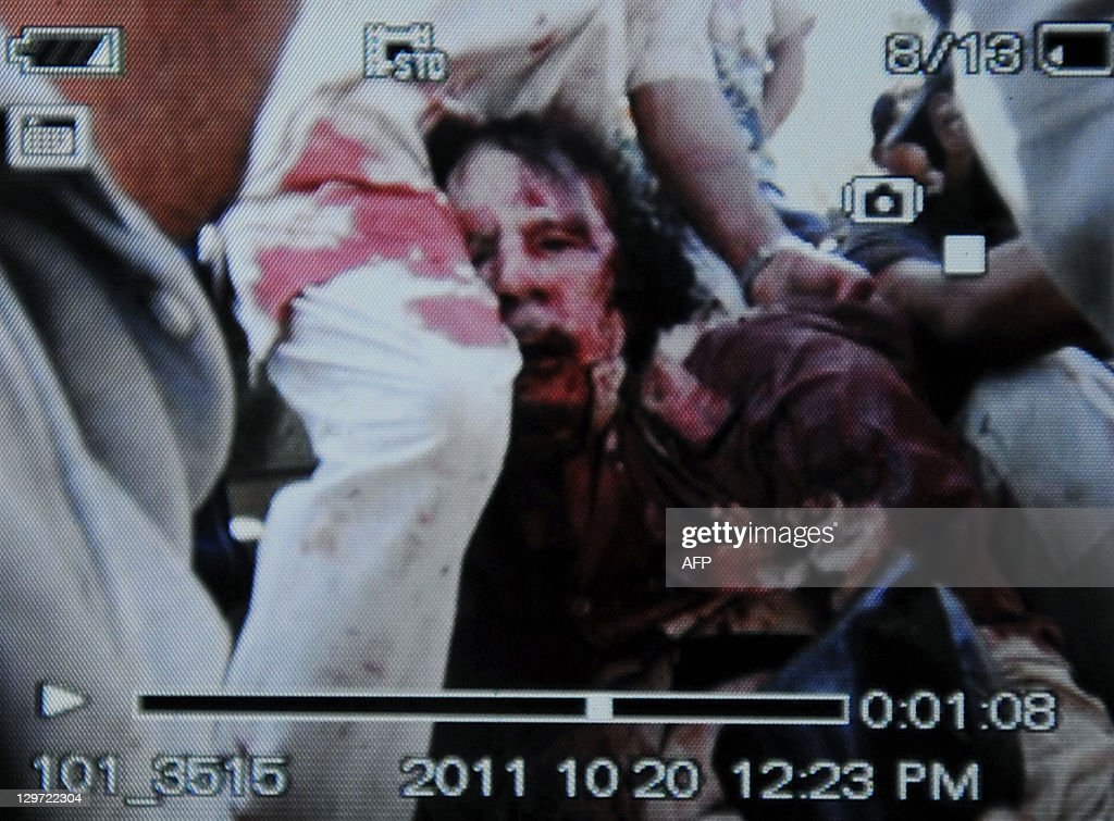 An image captured off a cellular phone camera shows the arrest of Libya's strongman Moamer Kadhafi in Sirte on October 20, 2011. A Libyan National Transitional Council (NTC) commander had told AFP that Kadhafi was captured as his hometown Sirte was falling, adding that the ousted strongman was badly wounded.