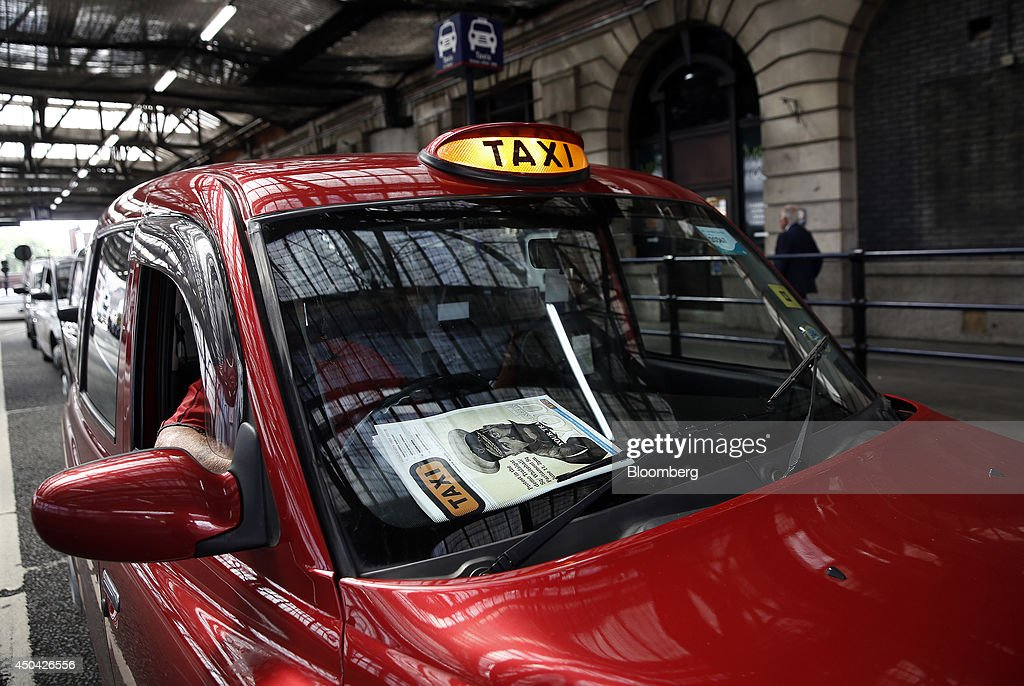 An image featuring military commander Horatio Kitchener and advertising today's taxi demonstration sits on the cover of the Taxi newspaper on the dashboard of a red London cab parked outside Waterloo train station, ahead of a protest against Uber Technologies Inc.'s car sharing service, in London, U.K., on Wednesday, June 11, 2014. More than 30,000 taxi and limo drivers from London to Milan plan to cause traffic snarls in tourist centers and shopping districts, in protest against the unregulation of Uber's car-sharing service. Photographer: Simon Dawson/Bloomberg via Getty Images