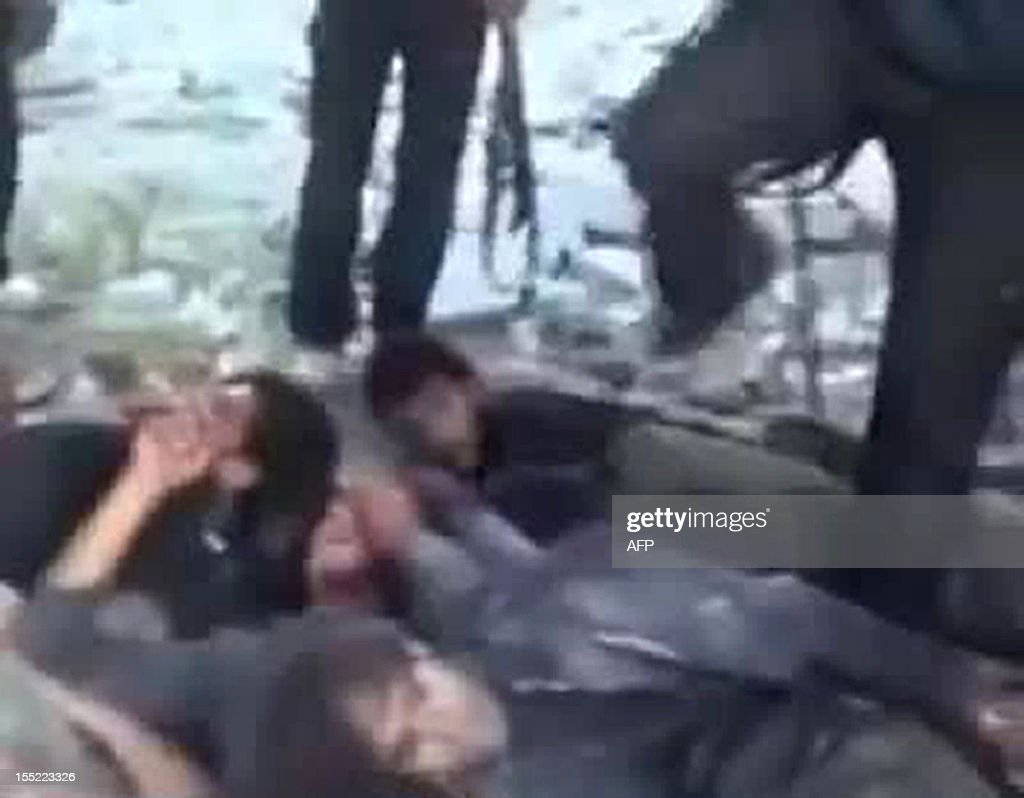 An image grab taken from a video dated on November 1, 2012 and uploaded on YouTube shows alleged Syrian government forces lying on the ground and being kicked before being executed by rebel fighters at the Hamisho checkpoint near Saraqeb. The video shows armed rebels kicking and executing their prisoners after they forced them to lie down in the destroyed structure of the checkpoint. AFP PHOTO/YOUTUBE CREDIT 'AFP PHOTO/YOUTUBE' - NO MARKETING NO ADVERTISING CAMPAIGNS - DISTRIBUTED AS A SERVICE TO CLIENTS - AFP IS USING PICTURES FROM ALTERNATIVE SOURCES AS IT WAS NOT AUTHORISED TO COVER THIS EVENT, THEREFORE IT IS NOT RESPONSIBLE FOR ANY DIGITAL ALTERATIONS TO THE PICTURE
