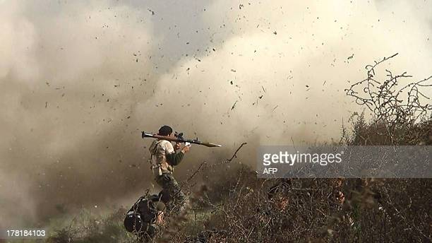 An image grab taken from a video shows opposition fighter holding a rocket propelled grenade as his fellow comrades take cover from an attack by...