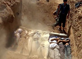 An image grab taken from a video uploaded on YouTube by the Local Committee of Arbeen on August 21 2013 allegedly shows Syrians covering a mass grave...