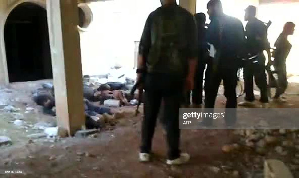 An image grab taken from a video uploaded on YouTube on November 1, 2012 shows rebel fighters gathering near alleged bodies of Syrian soldiers after they overran an army checkpoint in the northwestern Idlib province. Syria's northwestern Idlib province has become a key battleground in the country's conflict, especially after rebel forces seized the town of Maaret al-Numan on the Damascus-Aleppo road early last month. AFP PHOTO/YOUTUBE CREDIT 'AFP PHOTO/YOUTUBE' - NO MARKETING NO ADVERTISING CAMPAIGNS - DISTRIBUTED AS A SERVICE TO CLIENTS - AFP IS USING PICTURES FROM ALTERNATIVE SOURCES AS IT WAS NOT AUTHORISED TO COVER THIS EVENT, THEREFORE IT IS NOT RESPONSIBLE FOR ANY DIGITAL ALTERATIONS TO THE PICTURE