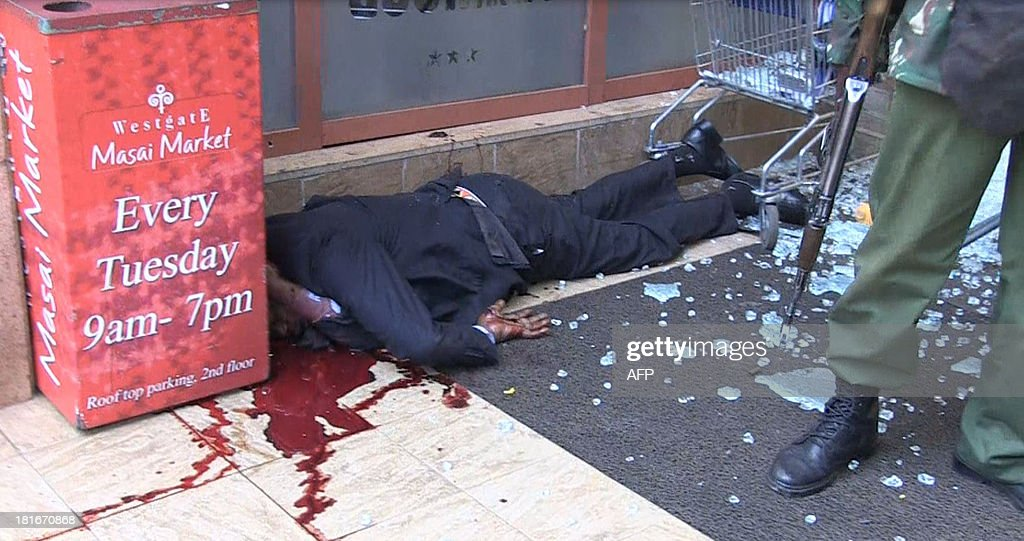 An image grab taken from AFP TV shows a Kenyan soldier standing next to a victim on September 21, 2013 inside the Westgate mall in Nairobi. Kenyan troops were locked in a fierce firefight with Somali militants inside an upmarket Nairobi shopping mall on September 22 in a final push to end a siege that has left at least 59 dead and some 200 wounded with an unknown number of hostages still being held. Somalia's Al Qaeda-inspired Shebab rebels said the carnage at the part Israeli-owned complex mall was in retaliation for Kenya's military intervention in Somalia, where African Union troops are battling the Islamists. AFP PHOTO/AFPTV/NICHOLE SOBECKI