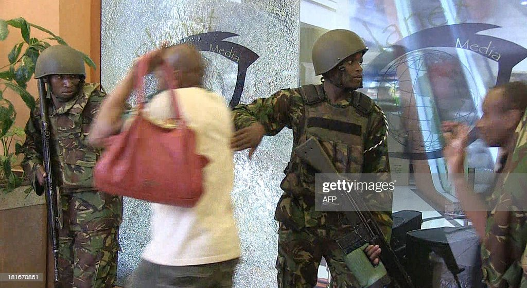 An image grab taken from AFP TV shows civilians being evacuated by military forces from a shopping mall following an attack by masked gunmen in Nairobi on September 21, 2013. Masked attackers stormed the packed upmarket shopping mall in Nairobi, spraying gunfire and killing at least 59 people and wounding 175 before holing themselves up in the complex.