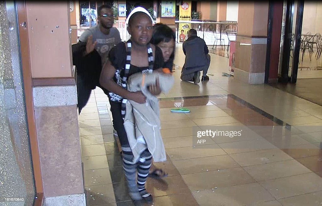 An image grab taken from AFP TV shows civilians taking cover following an attack by masked gunmen in a shopping mall in Nairobi on September 21, 2013. Masked attackers stormed the packed upmarket shopping mall in Nairobi, spraying gunfire and killing at least 59 people and wounding 175 before holing themselves up in the complex.