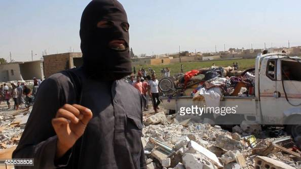 An image grab taken from an AFPTV video on September 16 2014 shows a jihadist from the Islamic State group standing on the rubble of houses after a...