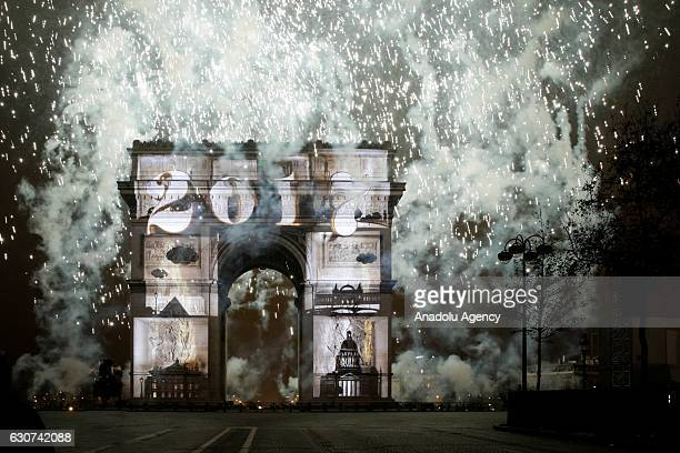 An image is projected on the Arc de Triomphe monument as fireworks light up the sky during a laser and 3D video mapping show on the theme of the...