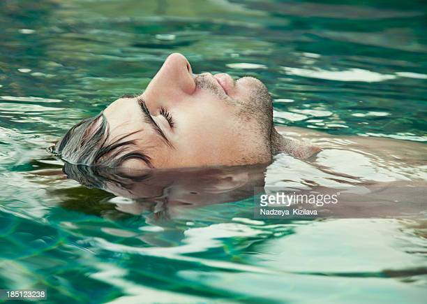 An image of a man with his eyes closed floating in water