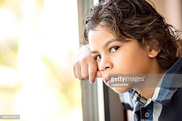 An image of a pensive little boy looking at the camera
