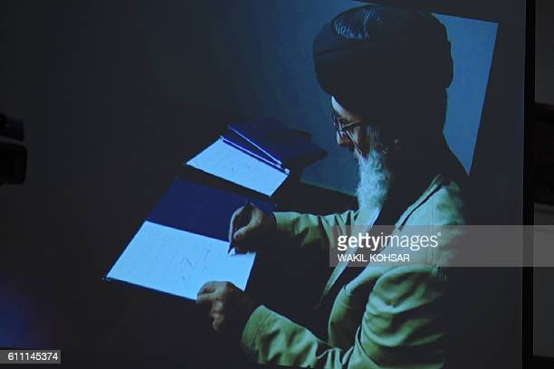TOPSHOT An image of Afghan warlord Gulbuddin Hekmatyar is displayed on a video projector screen from an undisclosed location as he signs a peace deal...