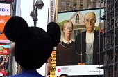 An image of 'American Gothic 1930' by Grant Wood is seen on an electronic billboard behind working cartoon macots as part of the 'Art Everywhere US A...