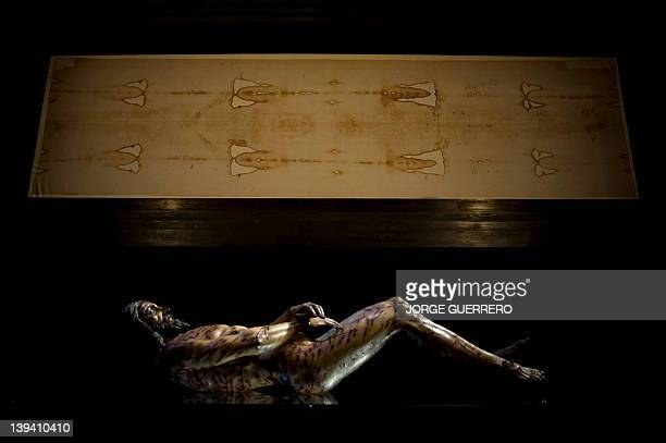 An image of Christ is displayed next to a facsimile of 'The Shroud of Turin' at the Cathedral of Malaga on February 20 2012 AFP PHOTO/ JORGE GUERRERO
