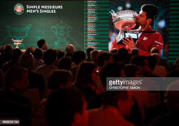 An image of defending French Tennis Open champion Serbian Novak Djokovic kissing the winner's cup is screened as people attend the official draw for...