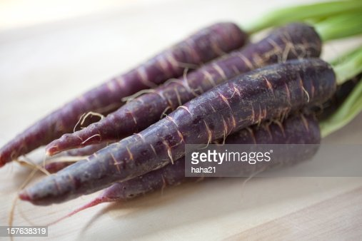 An image of four purple nutritious carrots