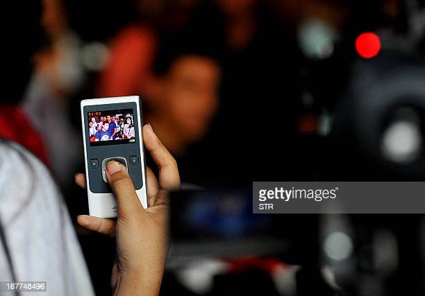 An image of Indian Bollywood film actor Aamir Khan is seen on a mobile phone as Khan interacts with fans and the media on completing 25 years in...
