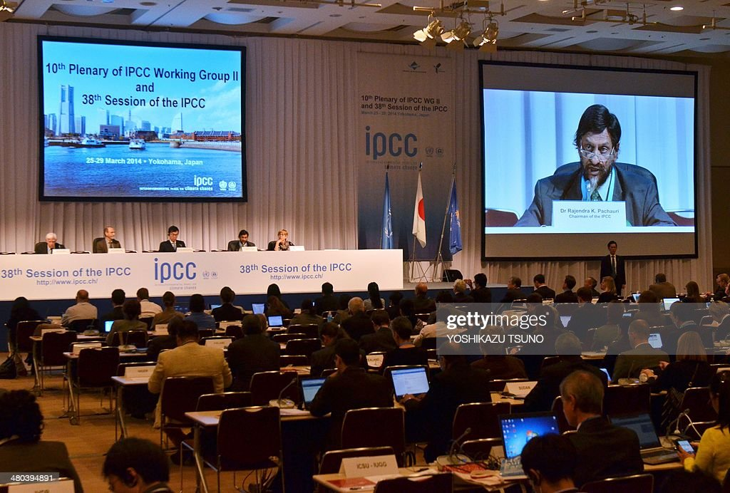 An image of Intergovernmental Panel on Climate Change (IPCC) chairman Rajendra Pachauri is projected onto a screen (R) as he delivers a speech at the opening session of the 10th plenary of the IPCC Working Group II in Yokohama, suburban Tokyo on March 25, 2014. International scientists gathered near Tokyo for a week-long meeting centred on a grim climate change report that warned of floods and drought that could stoke conflicts and wreak havoc on the global economy. AFP PHOTO / Yoshikazu TSUNO