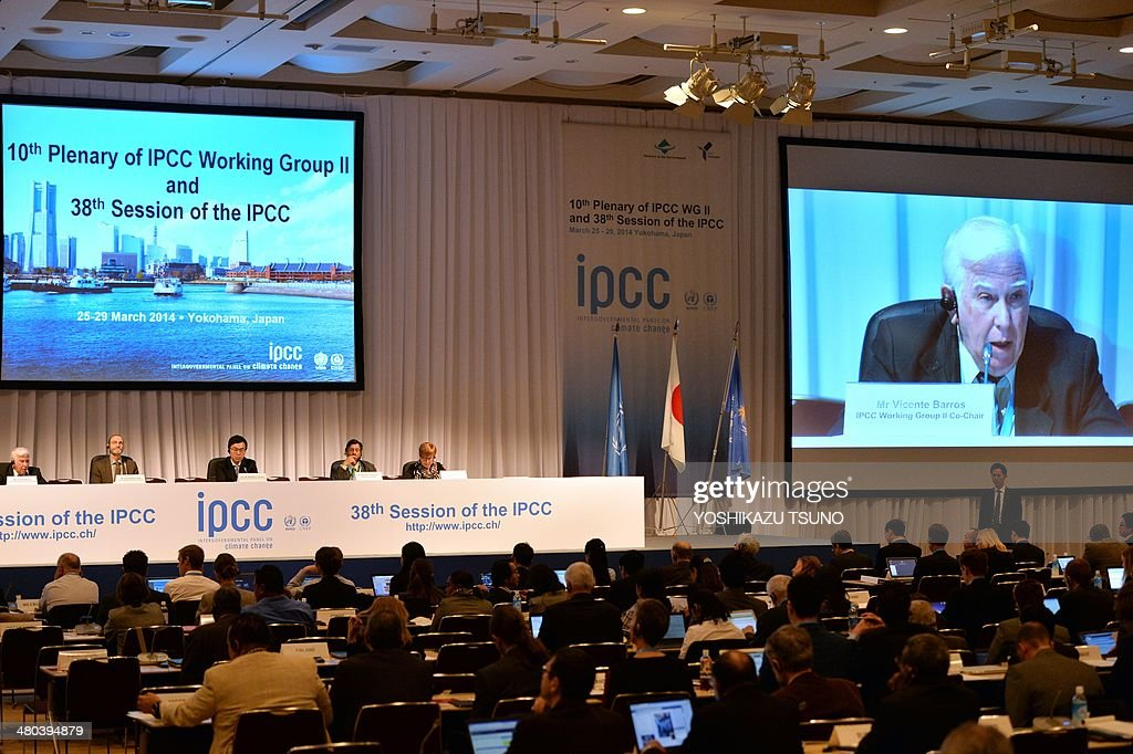 An image of Intergovernmental Panel on Climate Change (IPCC) Working Group II co-chairman Vicente Barros is projected onto a screen (R) as he delivers a speech at the opening session of the 10th plenary of the IPCC Working Group II in Yokohama, suburban Tokyo on March 25, 2014. International scientists gathered near Tokyo for a week-long meeting centred on a grim climate change report that warned of floods and drought that could stoke conflicts and wreak havoc on the global economy. AFP PHOTO / Yoshikazu TSUNO