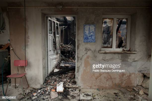 An image of Our Lady of Fatima remains at the entrance of a burnt house in the village of Vila Nova near Vouzela on October 16 2017 in Viseu region...