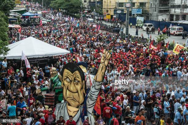 An image of President Rodrigo Duterte stands among thousands of protesters to air their concerns President Duterte delivers his second State of the...