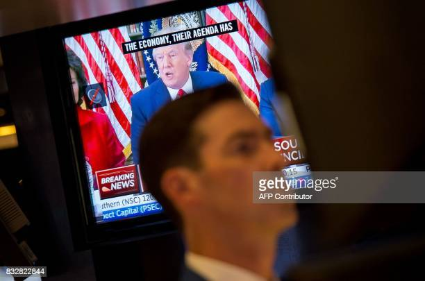 An image of President Trump is broadcast on the television as a trader works on the floor at the closing bell of the Dow Industrial Average at the...