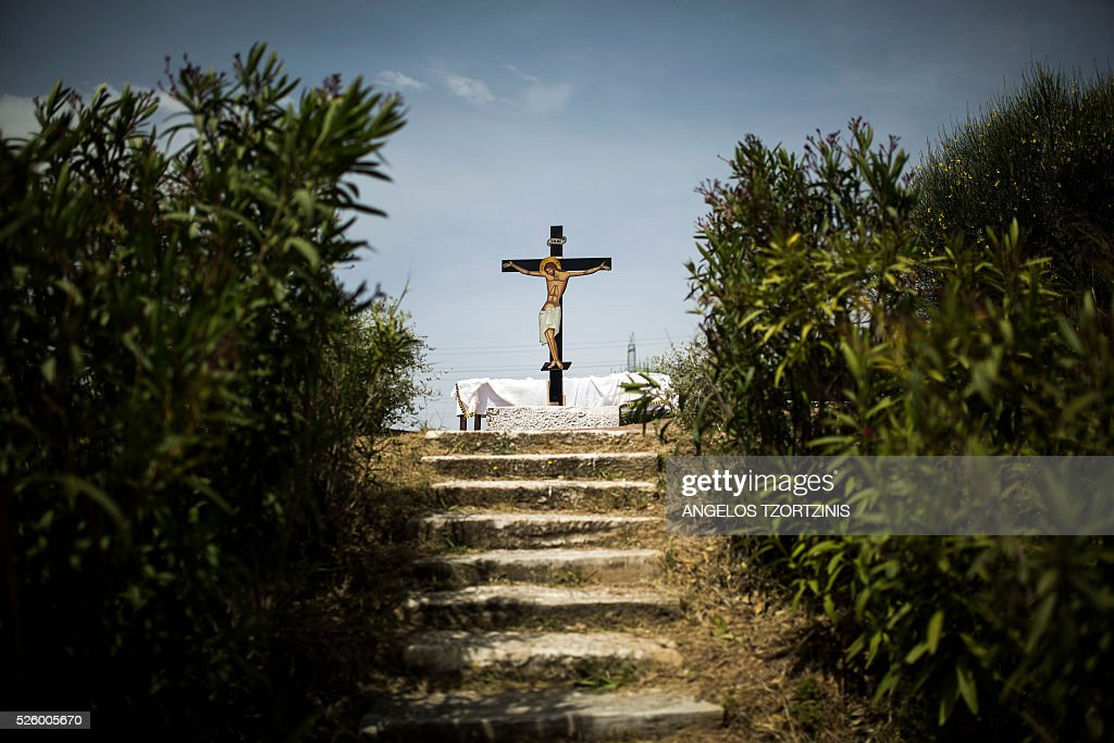 An image of the crucifixion of Jesus stands atop a hill during the ceremony marking the Apokathelosis, the removal of Christ's dead body from the Cross, which forms a key part of Orthodox Easter, during a ceremony at the Church of the Dormition of the Virgin in Penteli, northern Athens on April 29, 2016. Millions of Greeks flock to churches around the country this week to celebrate Easter, the country's foremost religious celebration. / AFP / ANGELOS