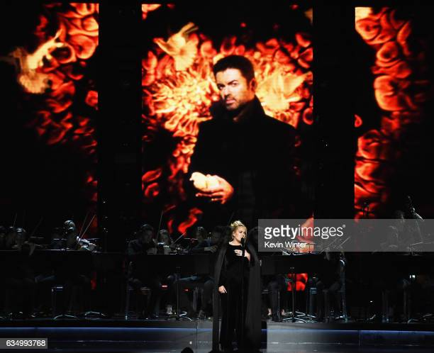 An image of the late George Michael is projected on a video screen while recording artist Adele performs onstage during The 59th GRAMMY Awards at...